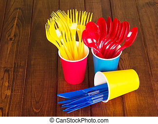 Multicolored, disposable cutlery and glasses on background...