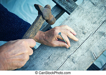 Closeup of mature man hands nails with old hammer - Closeup...
