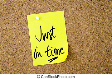 Just In Time written on yellow paper note pinned on cork...