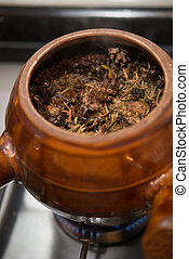 decocting medicinal herbs with enamel pot on gas burner