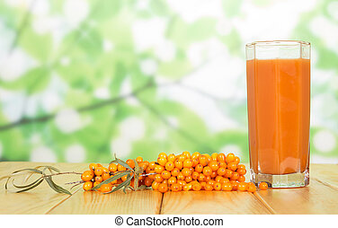 Bunch of sea buckthorn and glass juice from its berries on...