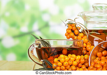 Bunches of sea buckthorn, a jug and cup with drink from her...
