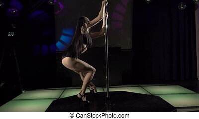 Professional woman pole dancer performing sensual dance on nightclub stage