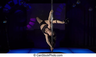 Sexy woman pole dancer performs sensual dance on night club...