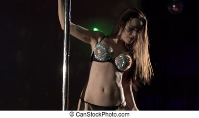 Sexy woman dancer performs sensual pole dance on lighted stage in night club