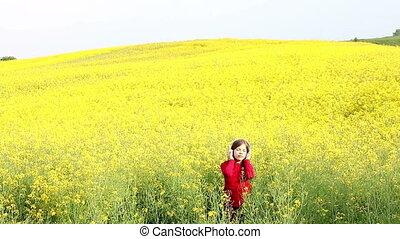 little girl enjoy in music on yellow field