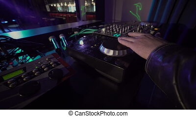 Close-up of DJ hands mixes the track on stage in night club...