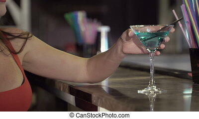 Close-up of a young woman enjoying drink at the bar in nightclub