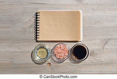 Food background. Blank open notebook for notes,salt,oil and sauce on a wooden table