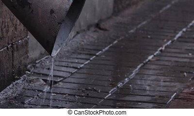 Rain water flowing from drain pipe closeup. passes by...