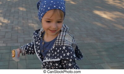 Little cute girl runs on the road, in the hands of her handbag, wearing a jacket with the stars.