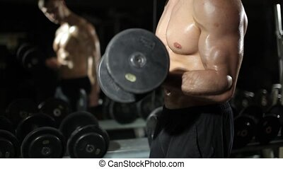Guy in the gym. Does exercises with dumbbells.