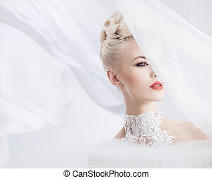 Elegant blonde with a bright veil on the head