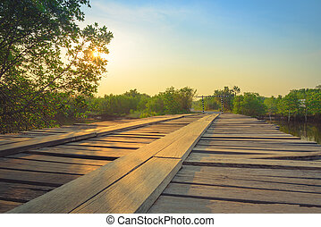 Wooden bridge in the countryside crossing the river at sunset. Selective focus. Vintage tone