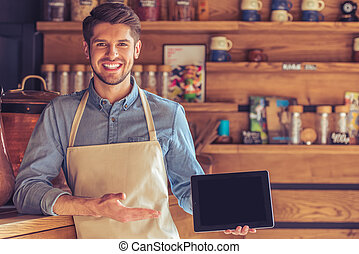 Handsome young waiter with gadget - Handsome young waiter in...