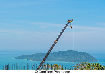 Crane on the blue sky and ocean.