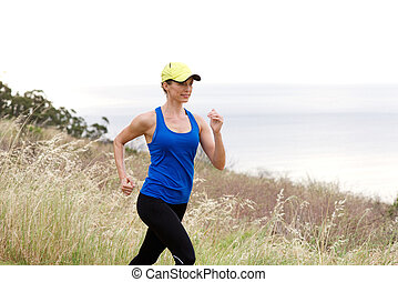 Smiling athletic woman jogging in nature - Portrait of...