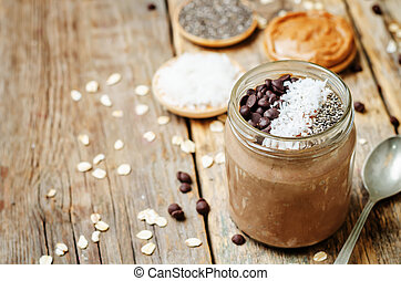 Chocolate Coconut Chia seeds overnight oats on a dark wooden...