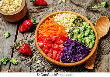 rainbow millet vegetable salad on dark wood background....