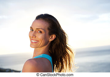 Woman looking over shoulder with sea in background