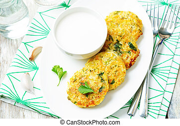 Cheesy millet zucchini fritters on a white wooden background...