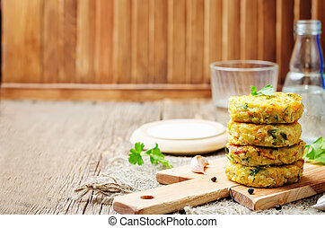 Cheesy millet zucchini fritters on dark wooden background...