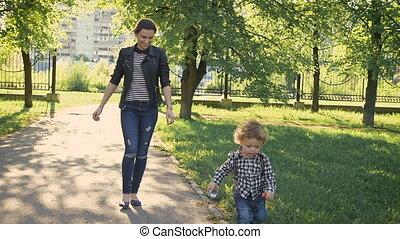 Melenko boy walking along a path in a park. Nice young girl...