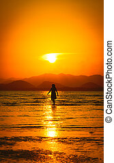 Silhouette of girl on the beach at sunset.