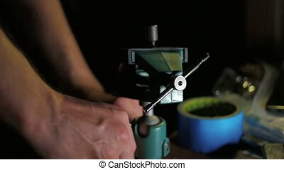 Man working with small diy hobby vice on table in dark room,...