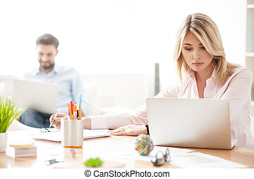 Cheerful young workers are using computers - Pretty blond...