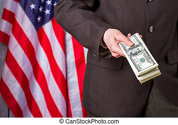 Businessman holding dollars beside flag US flag, person and...