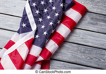 Creased and crumpled US flag. US banner on wooden...
