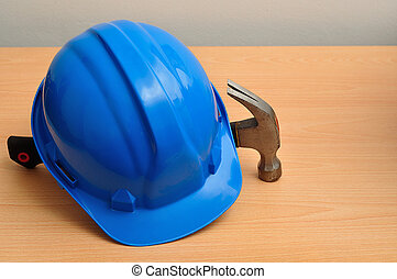 Blue hard hat and hammer - A blue hard hat displayed with a...
