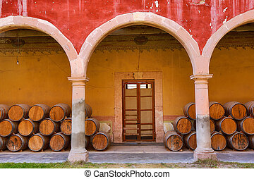 wooden barrels under the arches in mexico - colonial arches...