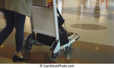 Passengers at Airport - Woman with a luggage trolley at the...