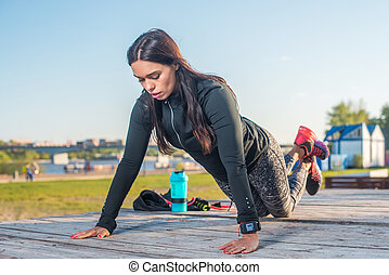 Fitness woman doing knee push-ups or press ups exercise...