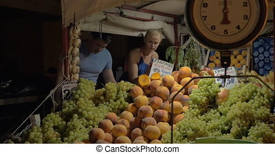 Couple choosing tomatoes on street market - Young family...