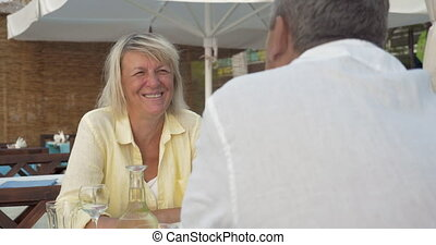 Senior couple having excited talk in summer cafe - Senior...