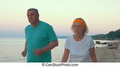 Mature Couple Jogging on the Beach - Steadicam shot of...