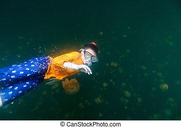 Child snorkeling in Jellyfish Lake - Underwater photo of...