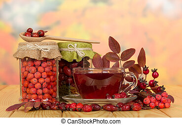 In glass jars rosehip berries, mountain ash and cup tea. -...