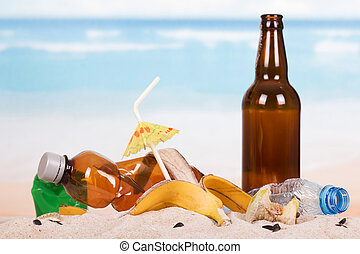 Beer bottle, food and household waste in sand on seashore -...