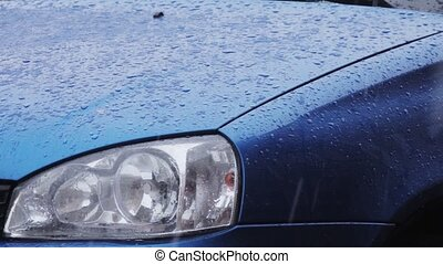 Water droplets form on blue car body.  HD