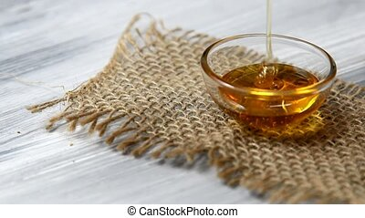 Honey pouring in a small bowl on a burlap cloth