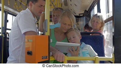 Family entertaining with tablet PC in the bus