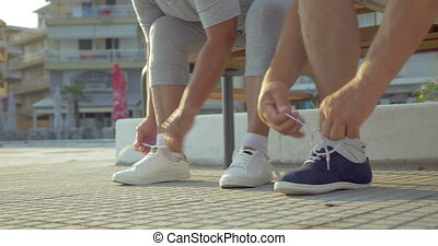 Senior man and woman lacing shoes before training -...