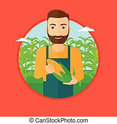 Farmer holding corn - A hipster man with the beard standing...