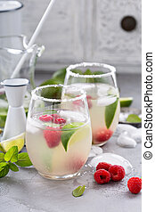 Cold summer cocktail with limes and raspberry