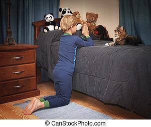 Bedtime Prayers - boy kneeling at bedside saying prayers in...