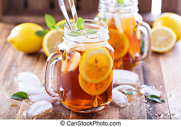 Iced tea with lemon slices and mint on rustic background